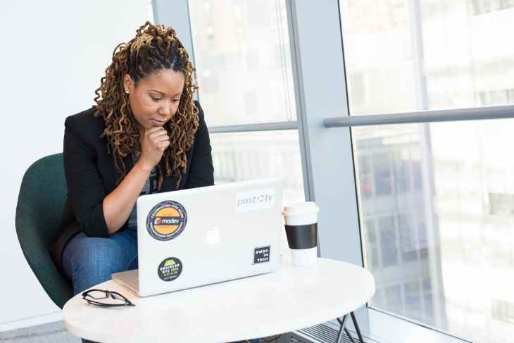 woman in black coat in front of white laptop computer